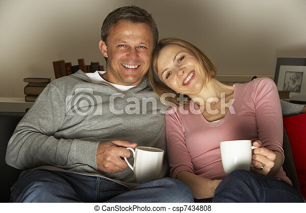 Couple With Coffee Mugs Watching Television - csp7434808