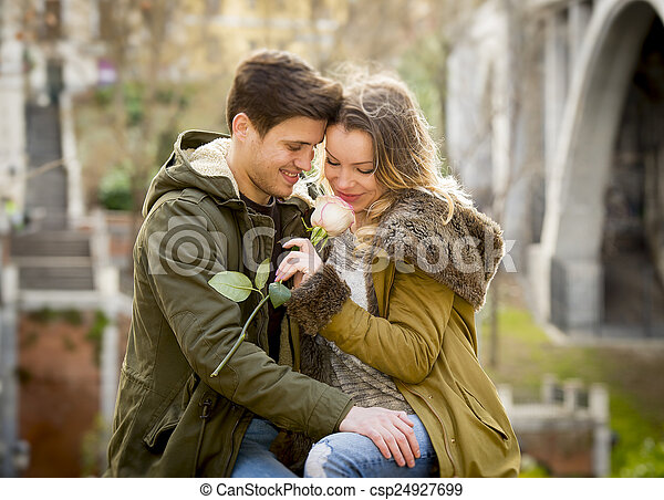 couple with rose in love kissing on street alley celebrating Valentines day with passion sitting on city park - csp24927699