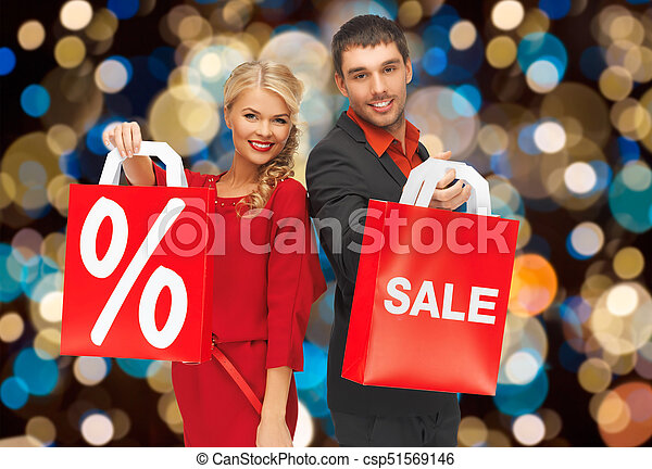 couple with sale and discount sign on shopping bag - csp51569146
