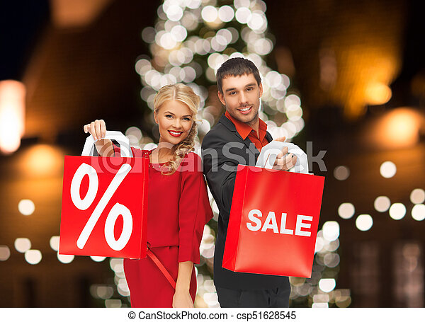 couple with sale and discount sign on shopping bag - csp51628545