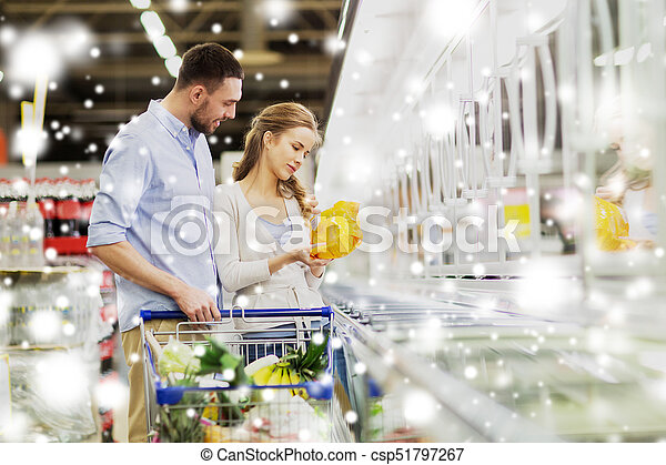 Couple With Shopping Cart Buying Food At Grocery
