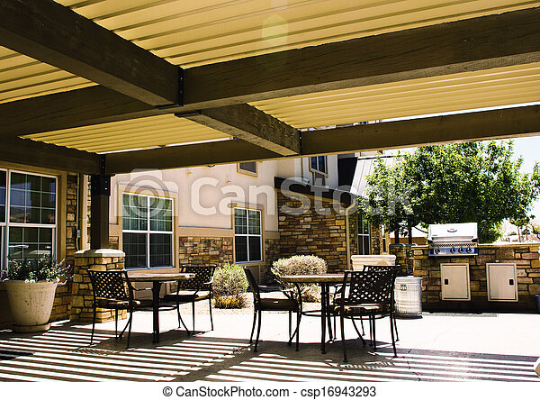 Covered hotel patio with tables - csp16943293