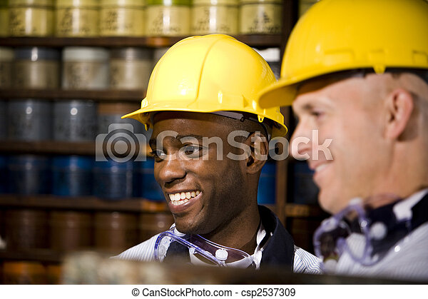 Coworkers in printing shop by shelves with inks - csp2537309