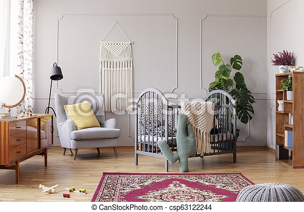 Cozy baby room with comfortable armchair with yellow pillow and grey wooden crib, real photo - csp63122244