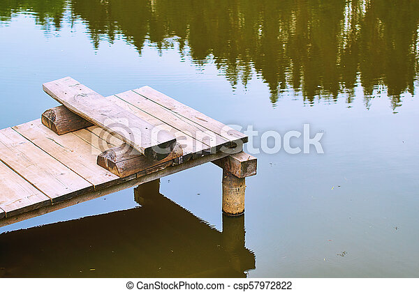 Cozy fishing bench on a wooden pier at the shore of a calm pond or lake in summer nountains - csp57972822