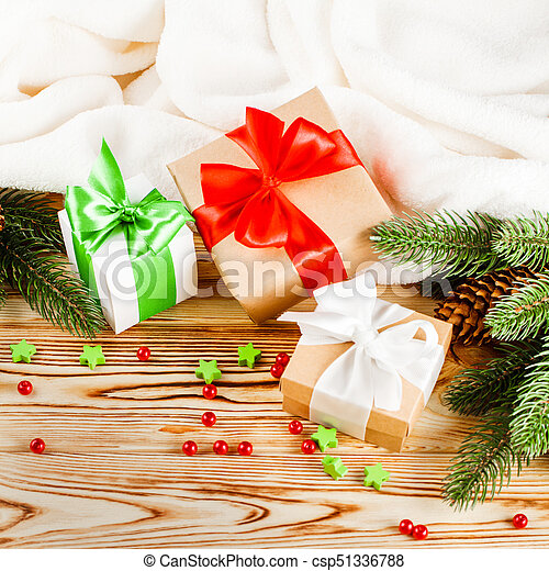 Craft gift boxes with color ribbon and bow, green Christmas tree, decorations, white plaid on wooden background. Xmas and New Year congratulation card, banner, flyer. - csp51336788