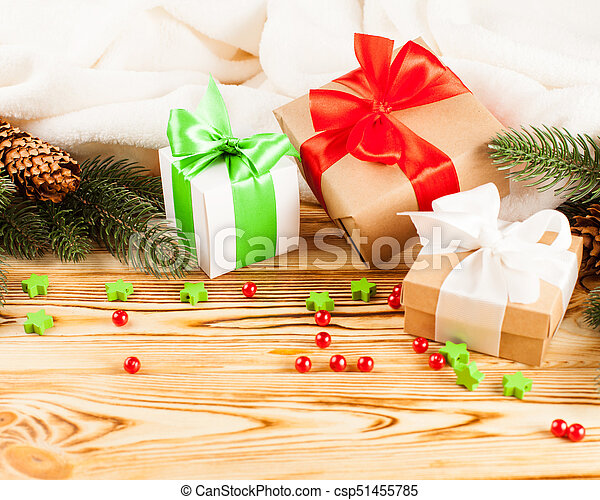 Craft gift boxes with color ribbon and bow, green Christmas tree, decorations, white plaid on wooden background. Xmas and New Year congratulation card, banner, flyer. - csp51455785