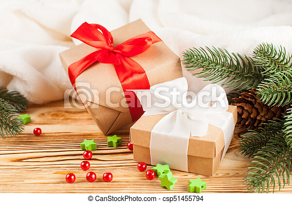 Craft gift boxes with color ribbon and bow, green Christmas tree, decorations, white plaid on wooden background. Xmas and New Year congratulation card, banner, flyer. - csp51455794
