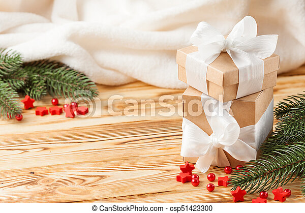 Craft gift boxes with red ribbon and bow, green Christmas tree, decorations, white plaid on wooden background. Xmas and New Year congratulation card, banner, flyer. - csp51423300