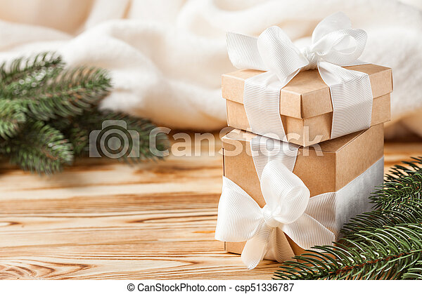 Craft gift boxes with white ribbon, bow, green Christmas tree, decorations, white plaid on wooden background. Xmas and New Year congratulation card, banner, flyer. - csp51336787