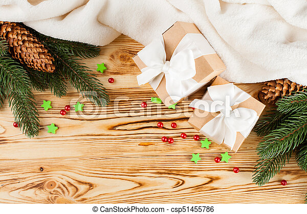 Craft gift boxes with white ribbon, bow, green Christmas tree, decorations, white plaid on wooden background. Xmas and New Year congratulation card, banner, flyer. - csp51455786