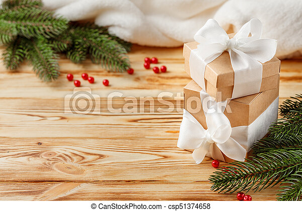 Craft gift boxes with white ribbon, bow, green Christmas tree, decorations, white plaid on wooden background. Xmas and New Year congratulation card, banner, flyer. - csp51374658