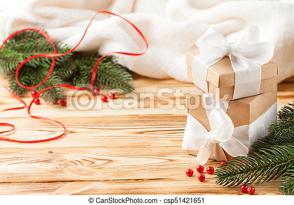 Craft gift boxes with white ribbon, bow, green Christmas tree, decorations, white plaid on wooden background. Xmas and New Year congratulation card, banner, flyer. - csp51421651