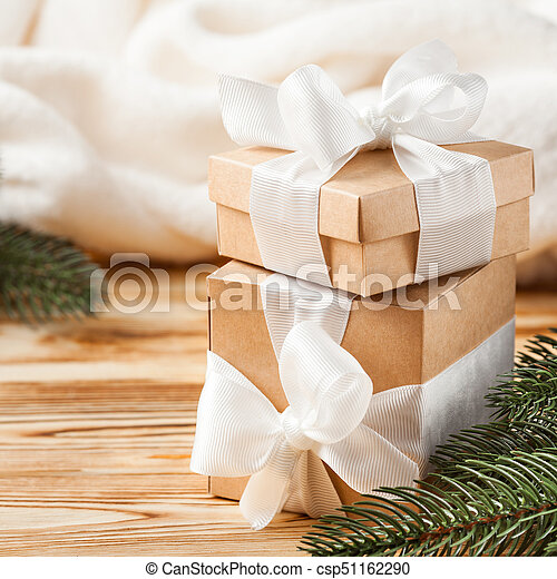 Craft gift boxes with white ribbon, bow, green Christmas tree, decorations, white plaid on wooden background. Xmas and New Year congratulation card, banner, flyer. - csp51162290