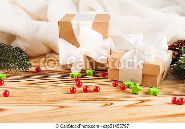 Craft gift boxes with white ribbon, bow, green Christmas tree, decorations, white plaid on wooden background. Xmas and New Year congratulation card, banner, flyer. - csp51455797