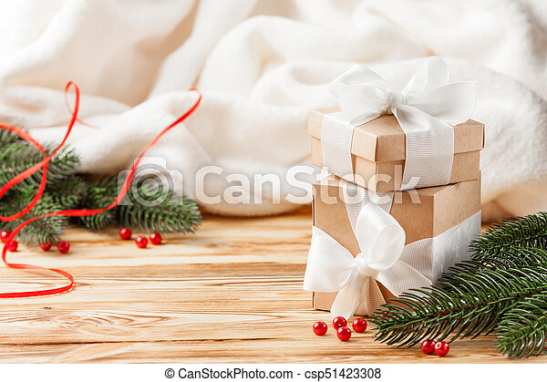Craft gift boxes with white ribbon, bow, green Christmas tree, decorations, white plaid on wooden background. Xmas and New Year congratulation card, banner, flyer. - csp51423308