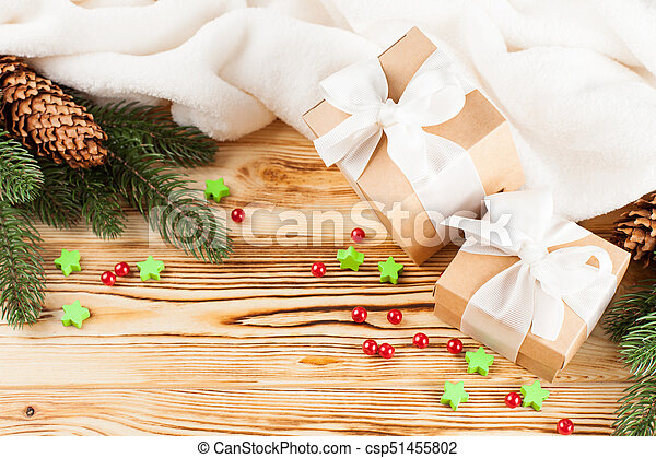 Craft gift boxes with white ribbon, bow, green Christmas tree, decorations, white plaid on wooden background. Xmas and New Year congratulation card, banner, flyer. - csp51455802