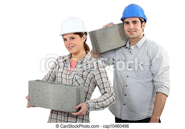 craftsman and craftswoman carrying heavy stone blocks - csp10460496