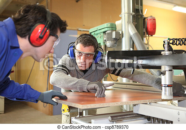 craftsman and his apprentice working together - csp8789370
