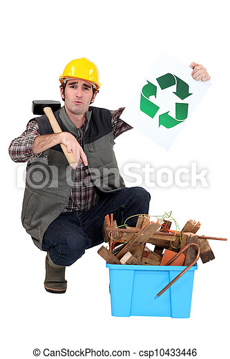 craftsman holding a recycling label and pointing at a box of used materials - csp10433446