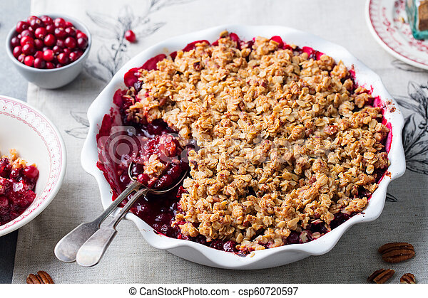 Cranberry crumble, crisp in a baking dish. Grey background. Close up. - csp60720597