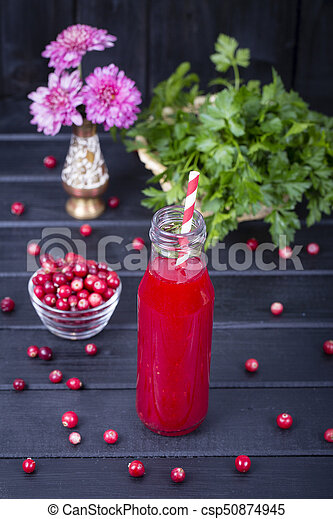 Cranberry juice in a glass bottle and raw cranberry on black wooden background, close up - csp50874945