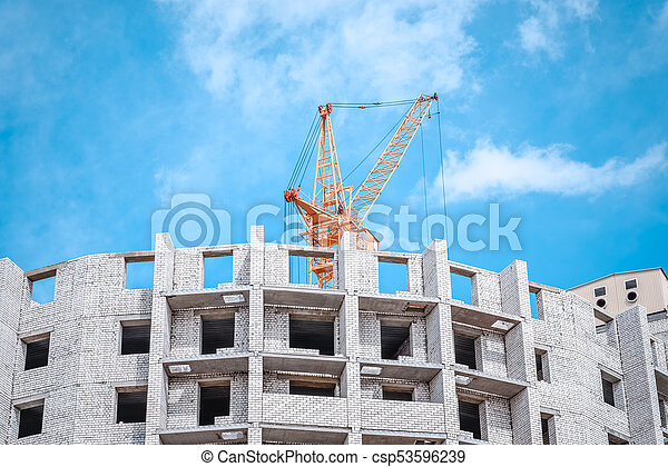 crane against sky building a new block of flats. new multi-storey house. Building crane and building under construction against cloudy sky. - csp53596239