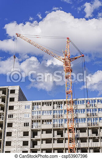 Crane and building construction site against blue sky - csp53907396