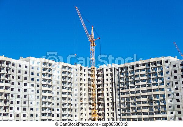 Crane and building under construction - csp86530312