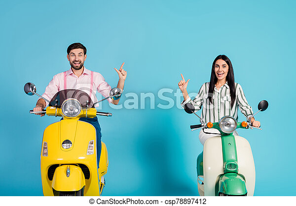 Crazy surprised shocked two people bikers drive power motor bike look incredible ads follow point index finger copyspace scream wow omg wear formalwear shirt isolated over blue color background - csp78897412