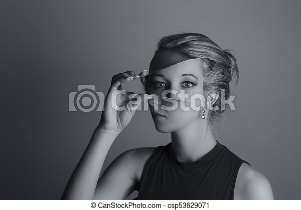Creative conversion of woman holding a shard of broken mirror and eyes from another exposure artistic conversion - csp53629071