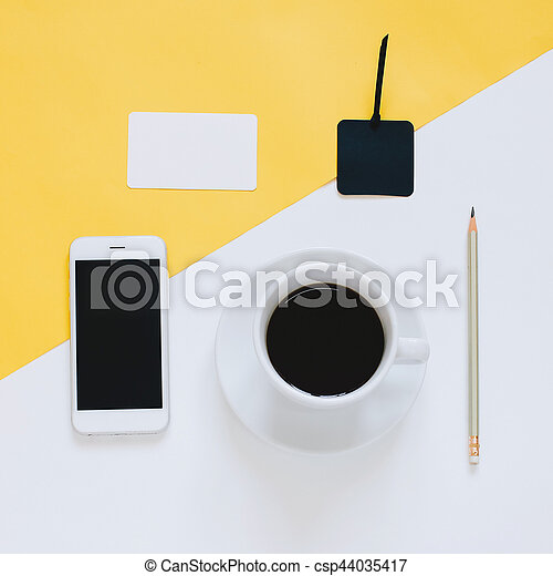Creative flat lay photo of workspace desk with smartphone, coffee and tag on yellow and white background, minimal styled - csp44035417