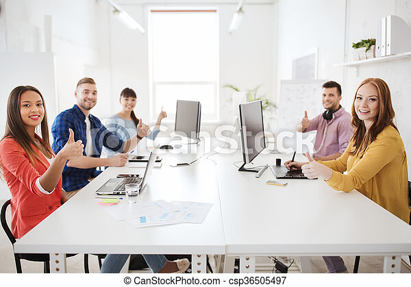 creative team with computers showing thumbs up - csp36505497