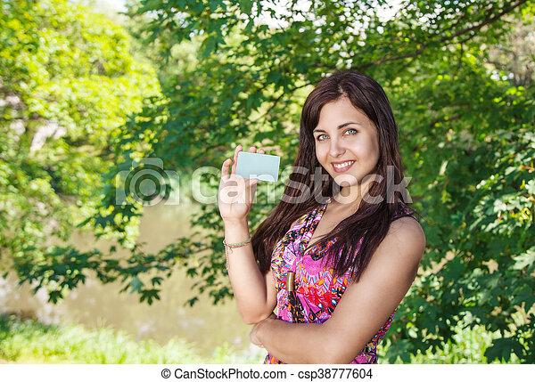 Una chica con una tarjeta de crédito en el parque - csp38777604