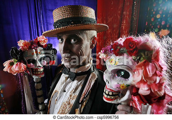 Creepy character in hay hat with a couple of hot skulls decorated with flowers. - csp5996756