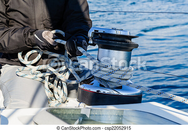 Crew work with genoa sheet rope and winch - csp22052915