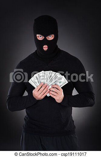 Criminal in a balaclava holding a fistful of money - csp19111017