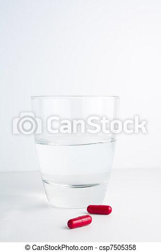 Pastillas rojas junto a un vaso de agua - csp7505358