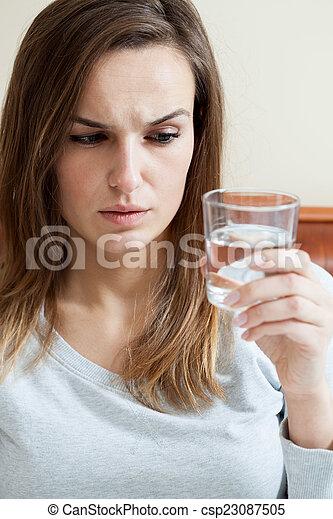 Mujer enferma sosteniendo un vaso de agua - csp23087505
