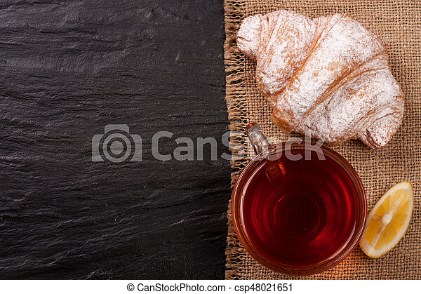croissant with a cup of tea on a black stone background with copy space for your text. Top view - csp48021651