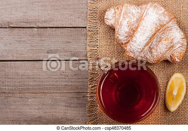 croissant with a cup of tea on an old wooden background with copy space for your text. Top view - csp48370485