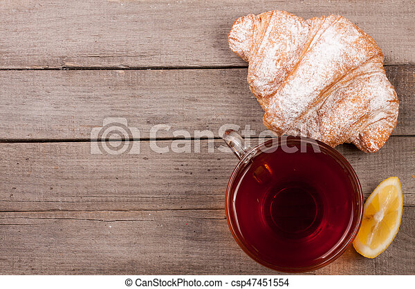 croissant with a cup of tea on an old wooden background with copy space for your text. - csp47451554