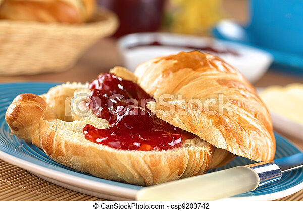 Croissant with butter and strawberry jam  - csp9203742