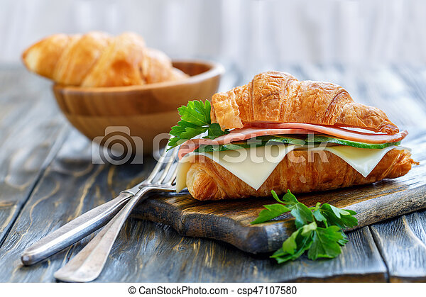 Croissant with ham, cheese and cucumber for breakfast. - csp47107580