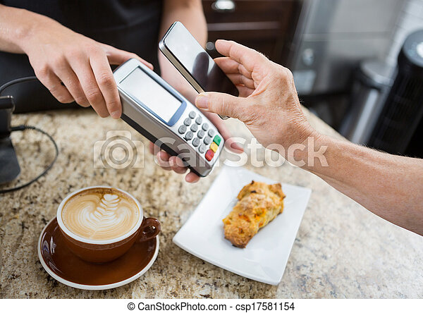 Cropped image of customer paying through mobilephone over electronic reader at cafe counter - csp17581154
