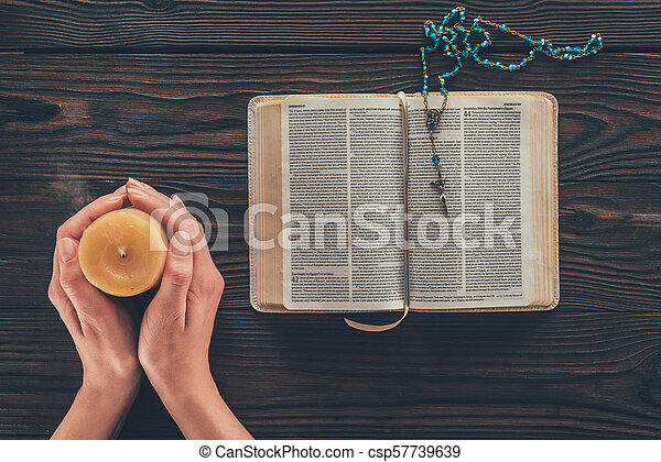 cropped image of woman holding candle above wooden table with bible - csp57739639