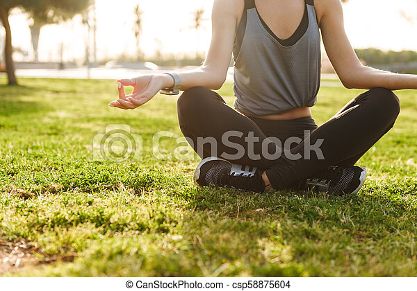 Cropped photo of young fitness woman meditate - csp58875604