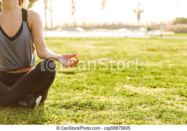 Cropped photo of young fitness woman meditate - csp58875605