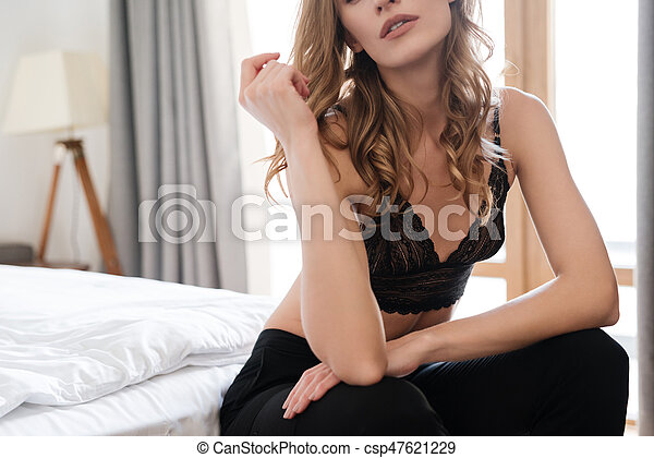 Cropped picture of woman sitting on bed - csp47621229