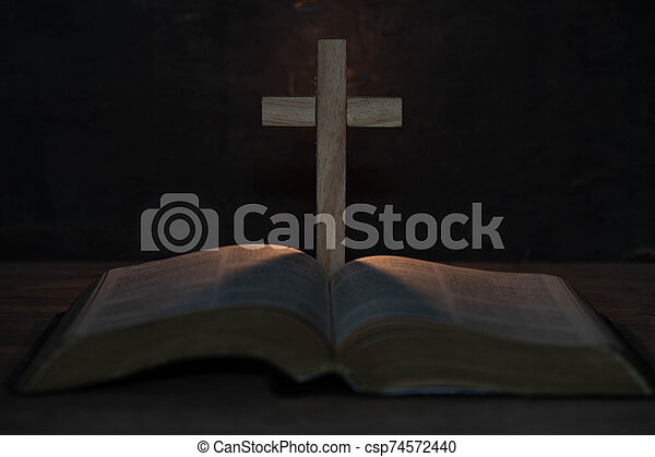 cross and holy Bible on wooden table - csp74572440